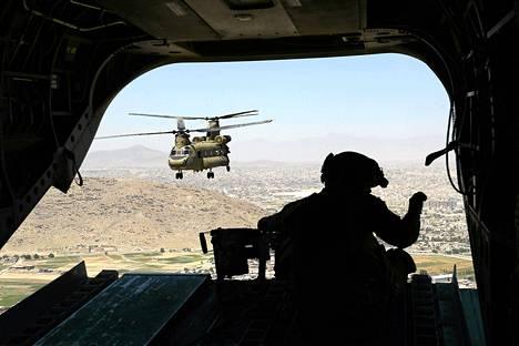 """Солдат натовских Международных сил содействия безопасности (ISAF) на вертолете """"Чинук"""" 11 августа в Афганистане."""