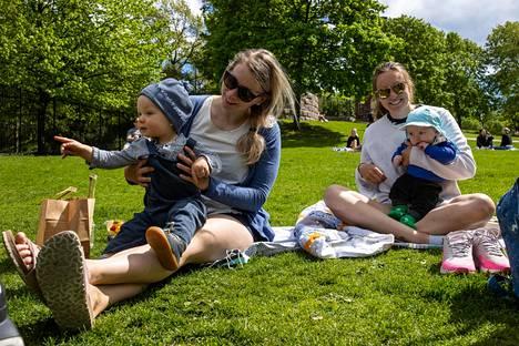 Laura Kaarion sylissä istuva yksivuotias Elias Kaario haluisi juoksennella pitkin puistoa. Noora Salonojan nelikuinen Oiva Joutsiniemi on ruokailuhetken jälkeen tyytyväinen.