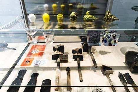 Edessä lasin valmistuksessa käytettäviä työkaluja. Taustalla sarja, joka kuvaa Oiva Toikan Kesäriekon syntyä.