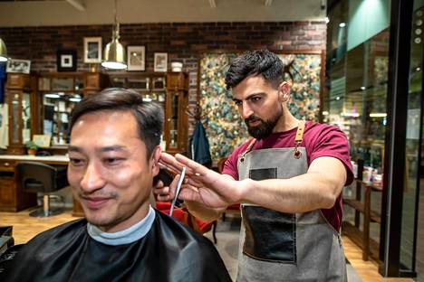 Parturi Luqman Hama Amin leikkasi Ngo Binhin hiuksia perjantaina Pasilan Triplassa.