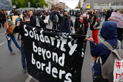 Mielenosoittajien lakanassa vaaditaan solidaarisuutta yli rajojen.