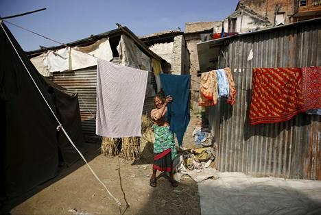 Nainen kuivatti pyykkiä hätämajansa edustalla Bhaktapurissa Nepalissa marraskuussa. Hänen talonsa tuhoutui maanjäristyksessä viime keväänä.