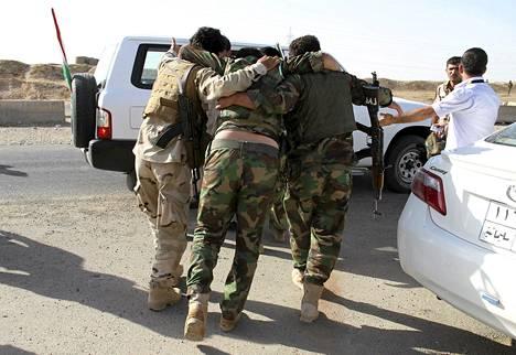 Kurdisotilaat auttoivat haavoittuneen kollegansa autoon Diyalan lähistöllä Irakissa lauantaina.