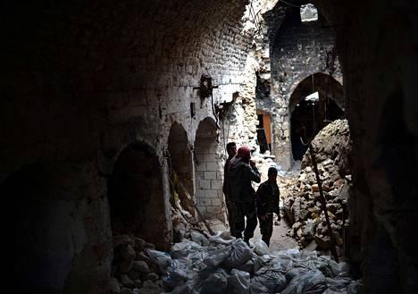 Kapinallistaistelijat seisoivat viime viikolla vaurioiden keskellä 1100-luvulla rakennetussa Umaijadimoskeijassa Aleppon vanhassakaupungissa. Moskeijan minareetti tuhoutui iskussa. Etualalla kapinallisten suojanaan käyttämiä hiekkasäkkejä.