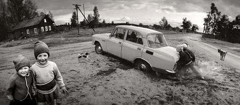 """Vuokkiniemi, Vienan Karjala, Neuvostoliitto 1991: """"Juopunut kuski oli ajanut Mossensa raitin lentohiekkaan. Lapset työntämään, koirat haukkumaan. Tytöt huomasivat kuvaajan ja juoksivat riemuissaan kuvaan. Vienan Karjalan 1990-luku toi mieleeni oman lapsuusajan 1950-luvun Suomessa."""""""