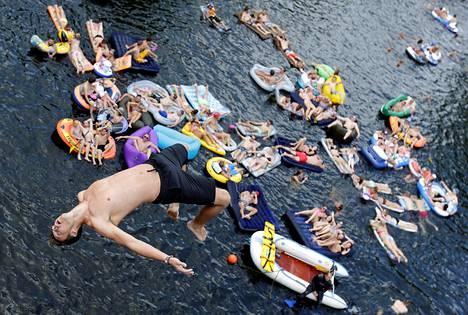 Ihmiset hyppivät veteen ennen uimahyppykilpailua Hrimezdicen kylässä Tšekin tasavallassa lauantaina.