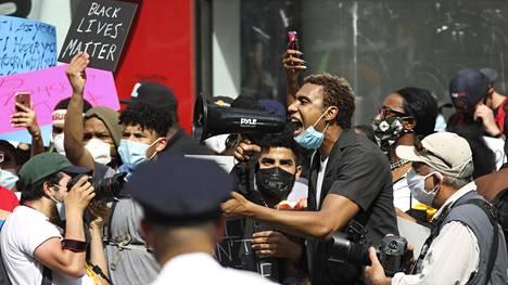 Mielenosoittajat huusivat iskulauseita poliiseille New Yorkissa perjantaina.