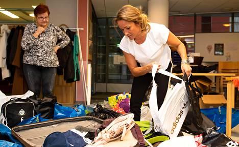 Heidi Jaari nostelee lahjoitetusta matkalaukusta hyväntekeväisyyteen tarkoitettuja tavaroita Merja Rantasalmen katsellessa. Naisten mukaan avunpyyntöjen määrä on kasvanut sen jälkeen, kun toimeentulotukea uudistettiin.
