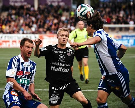 HJK:n Sebastian Mannström puski palloa. FC Lahden Loorents Hertsi ja HJK:n Teemu Tainio seurasivat katseella.