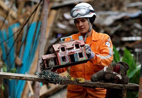 Pelastustyöntekijä kaivaa raunioista lelutalon etsiessään mutavyöryn uhreja kolumbialisessa Manizalesin kaupungissa torstaina.