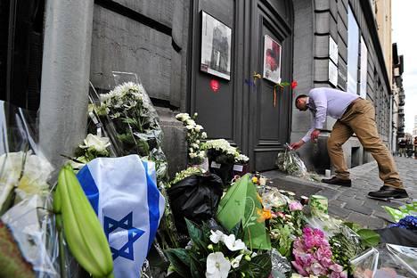 Mies jätti kukkia Brysselin Juutalaisen museon ovelle sunnuntaina.