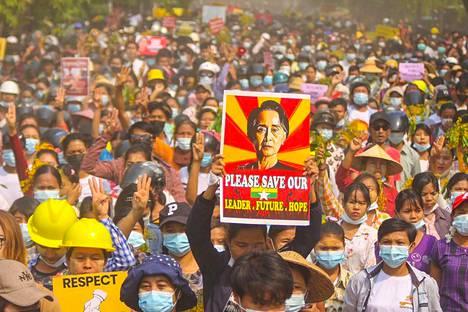 Mielenosoittajia Myanmarissa. Kyltissä Myanmarin syrjäytetyn johtajan Aung San Suu Kyin kuva.