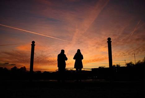 Pariskunta pysähtyi ihailemaan auringonlaskua Maschsee-järven yllä Saksan Hannoverissa maanantaina. Ilman lämpötila Saksassa on viime päivät pysystellyt nollan paikkeilla tai hieman yli.