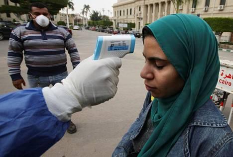Terveystyöntekijä tarkisti kehonlämmön ylempää korkeakoulututkintoa suorittavalla opiskelijalta Kairon yliopistolla sunnuntaina. Luennot keskeytettiin ainoastaan alempaa korkeakoulututkintoa suorittavilta.