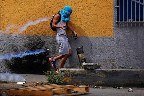 Mielenosoittaja väistelee poliisi ampumia kyynelkaasuammuksia Venezuelan pääkaupungissa Caracasissa maanantaina jatkuvissa protesteissa.