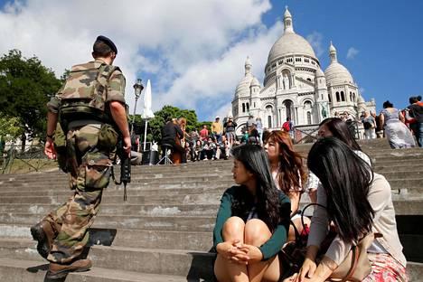 Korealaiset turistit seurasivat, kun sotilas nousi portaita kohti Sacre Coeurin katedraalia Pariisissa viikonloppuna.