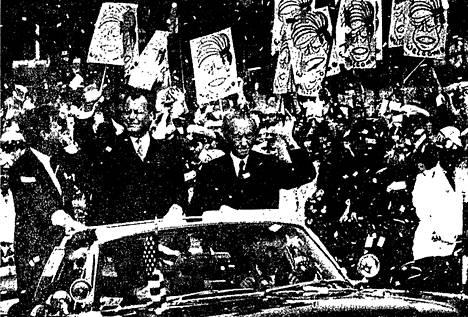 """Helsingin Sanomissa 27. kesäkuuta 1963 julkaistussa uutiskuvassa Kennedy seisoo vasemmalla. Kuvateksti kuului: """"Valtaviin Kennedyn tervetuliaistoivotuksiin antoivat oman värikkään leimansa taka-alalla näkyvät erään taidekoulun oppilaiden maalaamat muotokuvat, joissa lisäksi luki """"tervetuloa"""". Juhlinnan kohteina ovat vieraan lisäksi isännät, liittokansleri Adenauer (oik.) ja pormestari Brandt."""""""