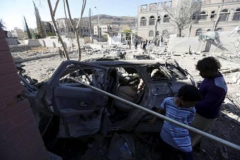 Pojat tutkivat tuhoutunutta autoa lauantaina tehdyn ilmaiskun jälkeen Jemenin pääkaupungin Sanaan liepeillä.