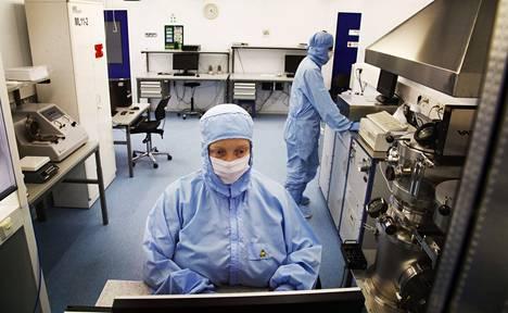Prosessiteknikko Anu Vilokkinen valmistaa lasersiruja Modulightin eristetyssä puhdastilassa. Suojavaatteita käytetään, jotta ylimääräiset hiukkaset kuten pöly eivät pääse tuhoamaan herkkiä lasersiruja.