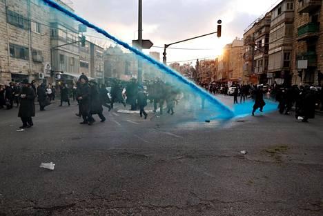 Ääriortodoksijuutalaisia mielenosoittajia rauhoitetaan torstaina vesitykillä Jerusalemissa.