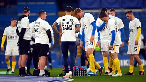 Brightonin pelaajilla oli jalkapallo on faneille -paidat ennen tiistai-illan ottelua Chelseaa vastaan. Samanlaiset paidat olivat maanantaina Leedsin pelaajilla.