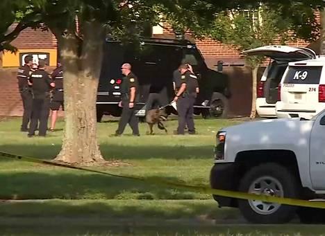 Poliisin koirapartio tutkii ammuskelupaikan ympäristöä Virginia Beachissä.