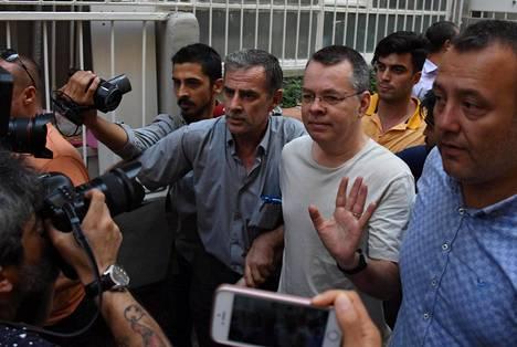 Pastori Andrew Brunson (kolmas vasemmalta) matkalla vankilasta kotiarestiin