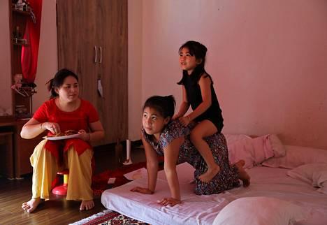 Licypriya Kangujam took her little sister Irina Kangujamin on her back at her home in the city of Noida on the outskirts of Delhi last September.  Next to them watched their mother Bidyarani Devi Kangujam Ongbi.