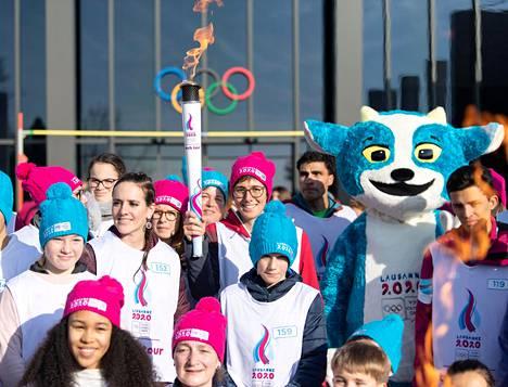 Nuorten talviolympialaiset alkavat Sveitsin Lausannessa torstaina. Ryhmä soihdunkantajia poseerasi keskiviikkona kisamaskotin kanssa olympiamuseon edustalla. Soihtua kantava urheilija on sveitsiläinen maastopyöräilijä Linda Indergand.