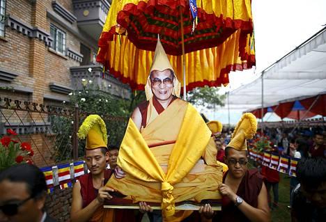 Tiibetiläiset munkit kantoivat Dalai Laman kuvaa tämän 80-vuotissyntymäpäiväjuhlan kunniaksi Kathmandussa maanantaina.
