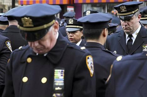 Osa murhatun poliisin Wenjian Liun hautajaisiin kerääntyneistä poliiseista käänsi selkänsä New Yorkin pormestarin Bill de Blasion pitäessä puhetta.