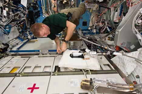 Astronautti Tim Peake säätää Kansainvälisen avaruusaseman järjestelmää, joka kierrättää vettä.