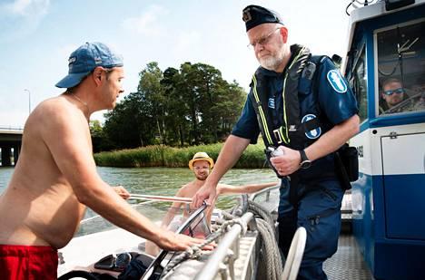 Vanhempi konstaapeli Jukka Grönlund pysäytti veneilemässä olleet Tom (vas.) ja Max Nymanin perustarkastusta varten.