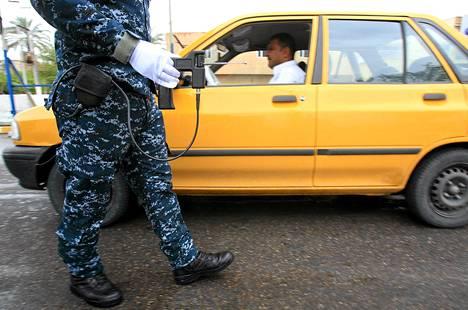 Irakilainen poliisi tarkasti autoa väärennetyllä pomminpaljastimella Baghdadissa perjantaina.