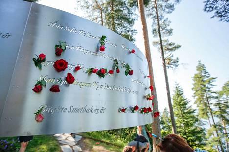 Muistotilaisuuteen torstaina osallistuneet jättivät ruusuja Utøyan saarella sijaitsevaan teokseen, johon on kaiverrettu saarella kuolleiden nimet.
