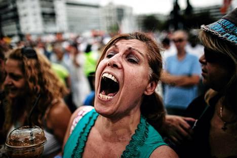 Mielenosoittaja huusi iskulauseita Kreikan parlamenttitalon edessä Ateenassa tiistaina.