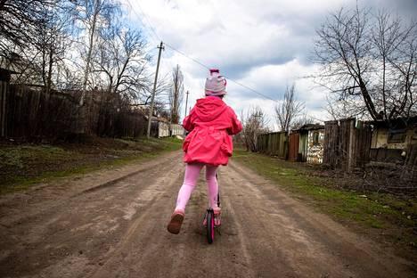 Viisivuotias Karolina ajaa potkulaudallaan Zolotessa, jonka kylien välistä kulkee Itä-Ukrainan sodan niin sanottu tulitaukolinja. Hän suuntaa kuvassa kohti kukkulaa, jonka laelta on suora näköyhteys kapinallisten asemiin.
