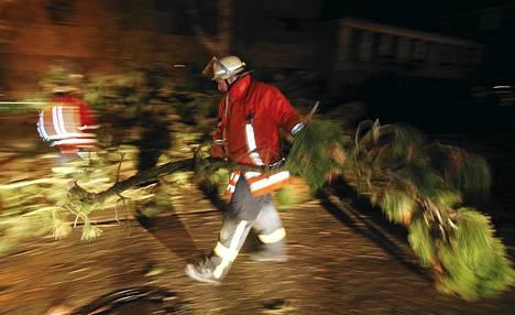 Palomiehet raivasivat tielle katkennutta puuta Sahlenburgissa lähellä Cuxhavenia Saksassa.