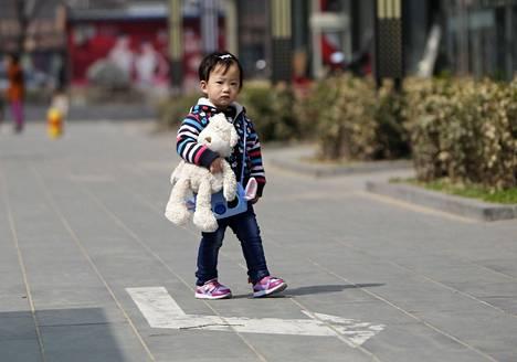 Pikkutyttö karhunsa kanssa Pekingissä huhtikuussa.