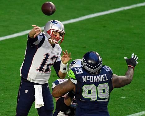 New Englandin Tom Brady (vas.) sinkoaa syötön ilmaan ennen kuin Seattlen puolustaja Tony McDaniel ehtii häntä estämään.