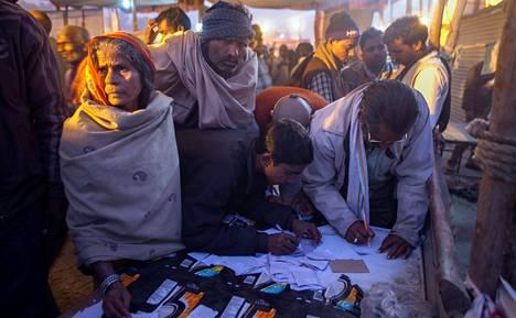 Hindupyhiinvaeltajat täyttivät tiistaina paperilapuille tietoja kadonneista omaisistaan Kumbhissa Intian Allahabadissa.