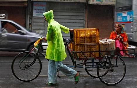 Mies kuljetti hedelmiä ja naista polkupyörällään Intian Ahmedabadissa tiistaina.