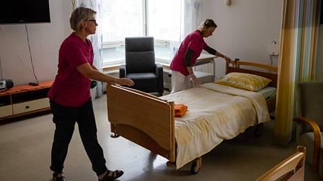 Sairaala-apulaisten tiiminvetäjä Tarja Enqvist ja vapaaehtoistoiminnan ohjaaja Nina Vuojela valmistelevat huonetta uutta potilasta varten.