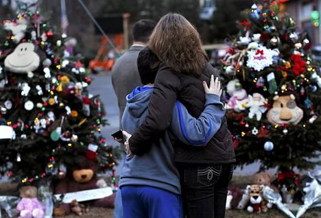 Nainen ja poika syleilevät kouluampumisen uhrien muistomerkillä Newtownissa.