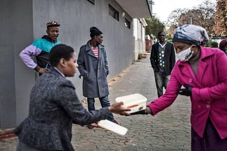 Vapaaehtoiset jakavat ruokapaketteja Johannesburgissa Etelä-Afrikassa.