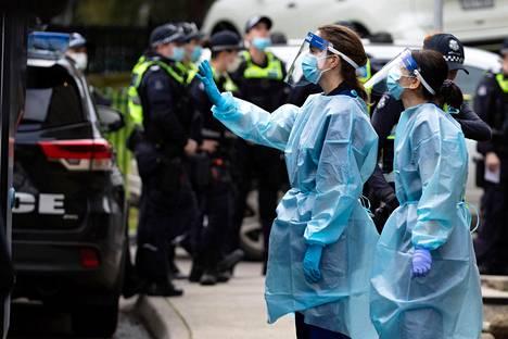 Terveyden huollon työntekijöitä Pohjois-Melbournen tornitalolähiön edustalla.