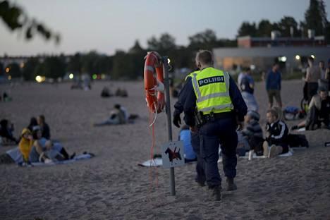 Poliisi partioi Hietaniemen uimarannalla, jonne kerääntyi nuorisoa juhannuspäivän iltana.