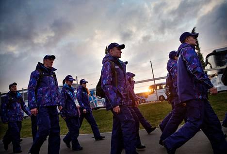 Violetteihin toppapukuihin pukeutuneita turvallisuusjoukkoja kulkee muodostelmassa Olympiapuistossa Adlerissa.