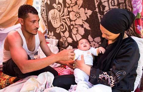 """Ali Moneer ja Heba Mansour hoitavat vauvaansa Mursin vastustajien leirissä Tahririn aukiolla. """"Mursi pilasi maan"""", Moneer manaa."""