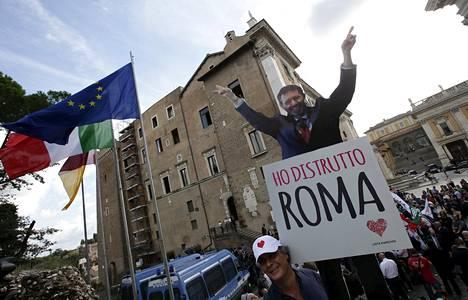 """""""Tuhosin Rooman"""", toteaa Rooman pormestaria Ignazio Marinoa esittävä kyltti. Kaupunkilaiset osoittivat mieltään Rooman kaupungintalon edessä 8. lokakuuta."""